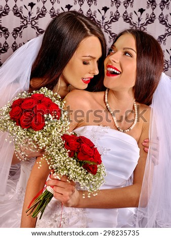 Wedding lesbians women in bridal dress on wallpaper background. - stock photo