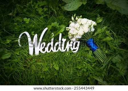 wedding letters with white flowers on grass. - stock photo