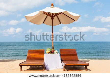 Wedding lunch on a sandy beach. Two loungers, parasol and a table with fruit.
