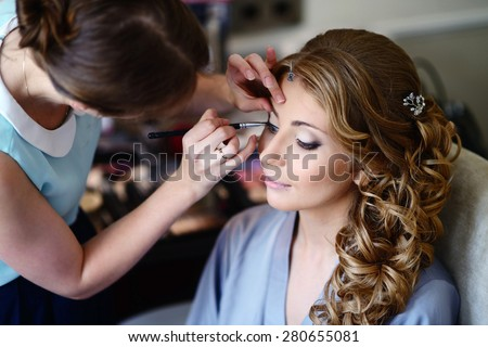 Wedding makeup artist making a make up for bride. Beautiful sexy model girl indoors. Beauty blonde woman with curly hair. Female portrait. Bridal morning of a cute lady. Close-up hands near face - stock photo