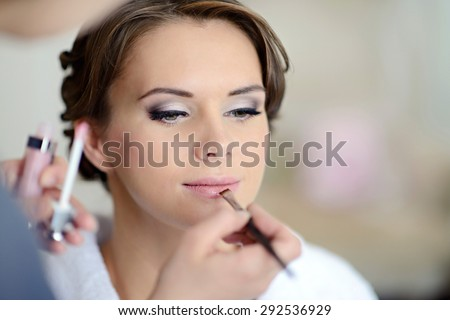 Wedding makeup artist making a make up for bride. Beautiful sexy model girl indoors. Beauty woman with curly hair. Female portrait. Bridal morning of a cute lady. Close-up hands near face - stock photo