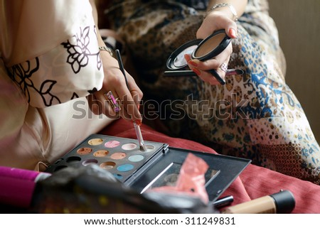 Wedding makeup artist making a make up for bride. Beautiful sexy model girl indoors. Beauty woman. Female portrait. Bridal morning of a cute lady. Close-up hands - stock photo