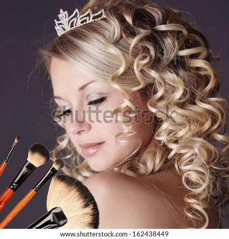 Wedding makeup portrait with brushes.