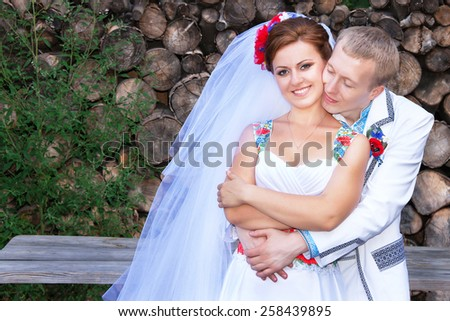 Wedding (married ) couple. Caucasian happy bride and groom in the ukrainian style (dress, suit) with embroidered are standing outdoors. Female (woman )and male (man) models in their 20s. Ukraine. - stock photo
