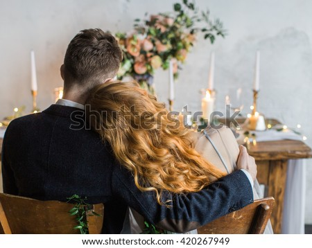 Wedding. Night. Engagement. The bride and groom in a wedding dress sitting at served table with candles and bouquet, shot from the back. bride put her head on his shoulder - stock photo