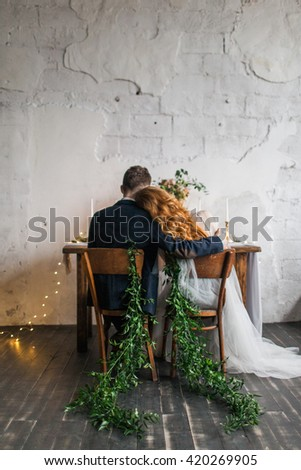 Wedding. Night. Engagement. The bride and groom in a wedding dress sitting at served table with candles and bouquet, from the back. bride put her head on his shoulder. Chairs with green branches - stock photo