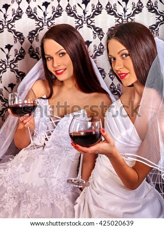 Wedding of lesbians girl in white long bridal dress keeps red wine glass. Wallpaper background. - stock photo