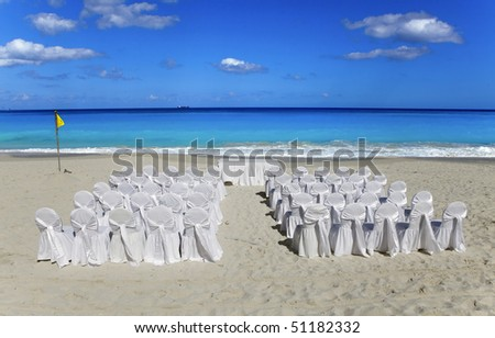 Wedding on tropical beach.  Chairs and tables in expectation of visitors. - stock photo
