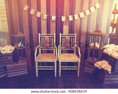 "Wedding or love concept image. The twin antique chairs against  words card of ""Just married"" hang on wooden wall with sweet rose flowers is all around. Vintage or retro style and filtered process.  - stock photo"
