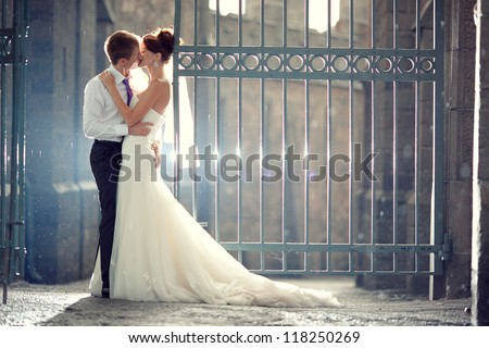 wedding pair hugging and kissing at the gate - stock photo