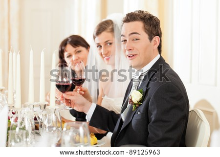 Wedding party at dinner - the bridal couple with guests - stock photo