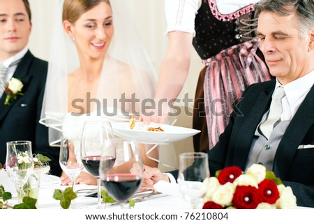 Wedding party at dinner - the dish is going to be served - stock photo