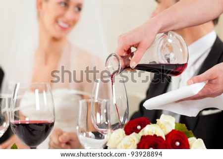 Wedding party at dinner - wine is be poured into glasses - stock photo