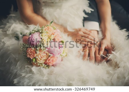 Wedding pastel bouquet closeup in front of couple - groom and bride's hands with elegant manicure. Flowers lay on the dress with swan feather decor - stock photo