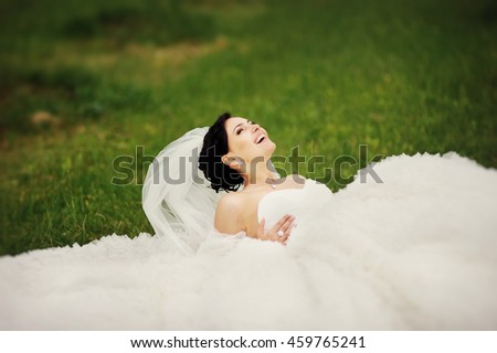 Wedding Photo Beautiful young brunette bride wearing white dress laying on grass in garden - stock photo