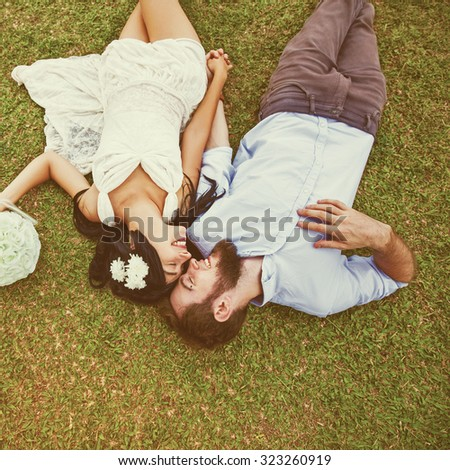 "wedding photo of couple on a grass. ""Instagram"" style filter applied - stock photo"