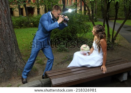 Wedding photo session, a bridegroom with a camera in hand, photographing the bride. - stock photo