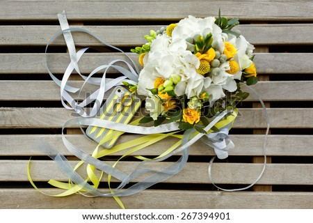 wedding photo set in yellow and gray colours: rings, telephone case and bouquet of roses, Craspedia, Hydrangea, Brunia silver flowers - stock photo