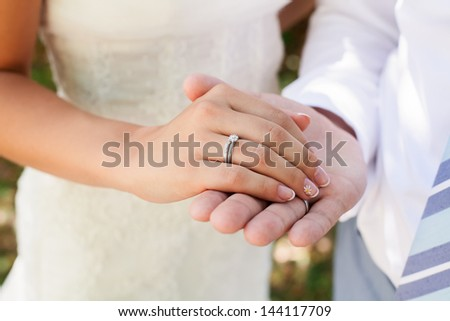 Wedding photograph of a young couple of lovers who are just married, are close to each other in harmony, love and happiness. Groom holds the bride's hand in his hand. - stock photo