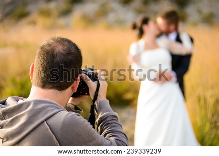 Wedding photographer taking photographs of groom and bride - stock photo