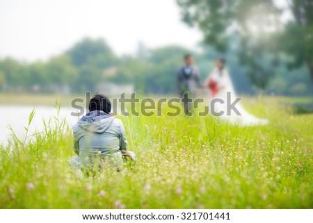 Wedding photographer taking photographs of groom and bride - stock photo