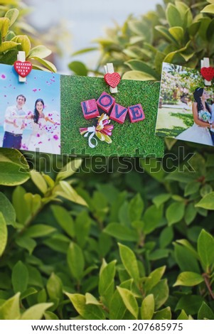 wedding photos hanging (focus on the middle photo) - stock photo