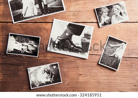 Wedding photos laid on a table. Studio shot on wooden background. - stock photo