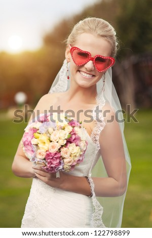 wedding: playful beautiful bride in white wedding dress with bouquet hairstyle and bright makeup waiting for groom. alluring blond woman in bridal dress and fresh flowers posing outdoors smiling - stock photo