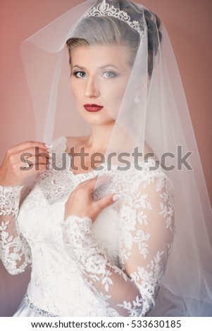 Wedding portrait of the happy bride in a white dress and veil