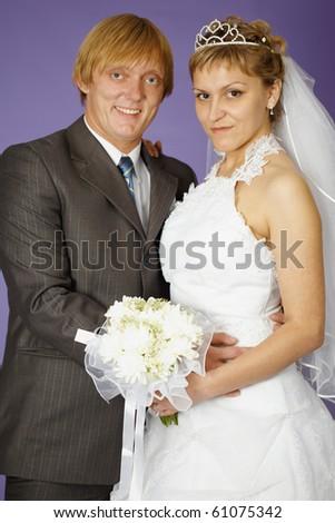 Wedding portrait of the newlyweds on a purple background - stock photo