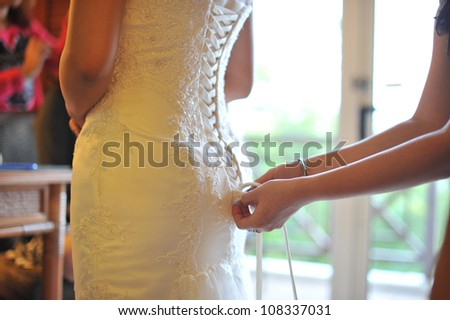 Wedding preparation, wedding gown being tied up - stock photo