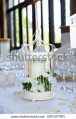 Wedding reception decoration of candle with white flowers on table closeup - stock photo