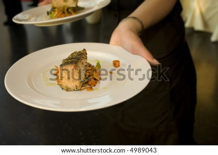 Wedding Reception fine dinning with first course of succulent salmon steak being served - stock photo