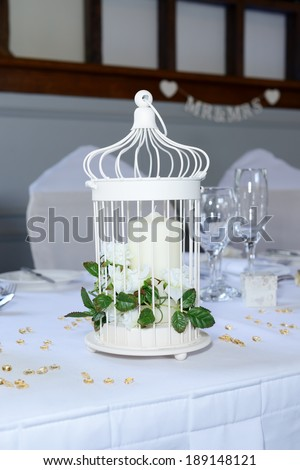 Wedding reception table closeup with details and decorations including candle and white flowers