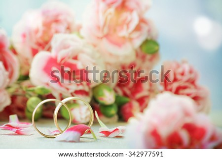 wedding ring against flower background - stock photo