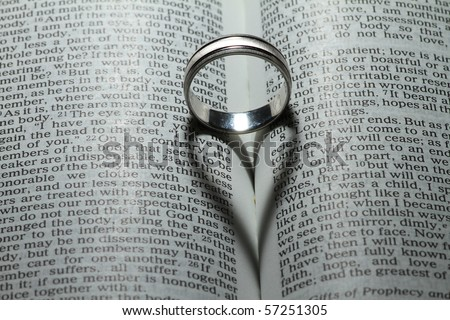 """Wedding ring casting a heart onto a bible. """"Love never ends"""" verse - stock photo"""