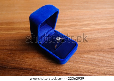 wedding ring in the box on wooden table - stock photo