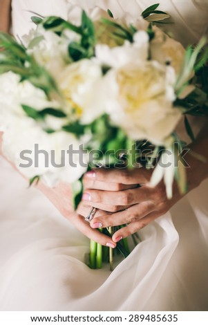 wedding ring on bride hand with  bouquet of white peony close up
