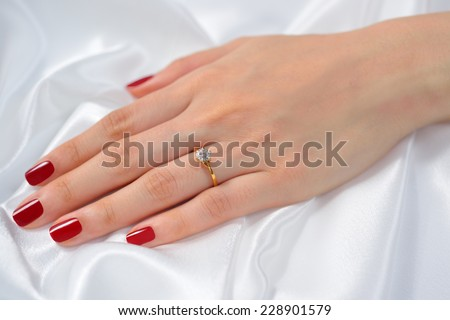 Wedding ring on hand of bride on white cloth - stock photo