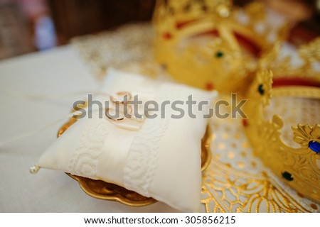 wedding ring on pillow near crown of newlyweds - stock photo