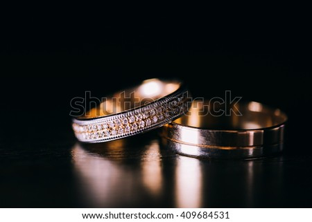 Wedding ring with diamonds on a wooden table, close-up macro - stock photo