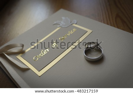 wedding rings and an order of service