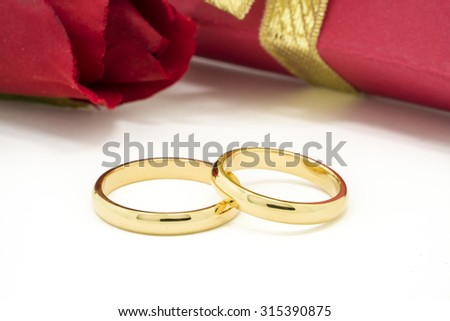 Wedding rings and artificial rose on white background, horizontally Selective focus - stock photo