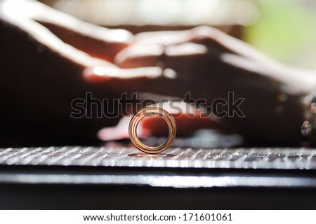 wedding rings and bride and groom's hands on table - stock photo