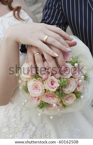 wedding rings and couple with bouquet - hands in foreground