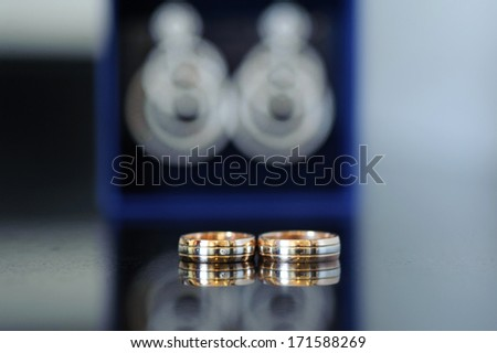 wedding rings and earrings in box on table - stock photo