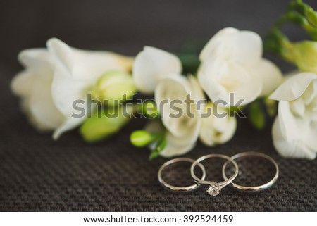 Wedding rings and engagement ring in focus, white flowers on background. Shallow focus. - stock photo