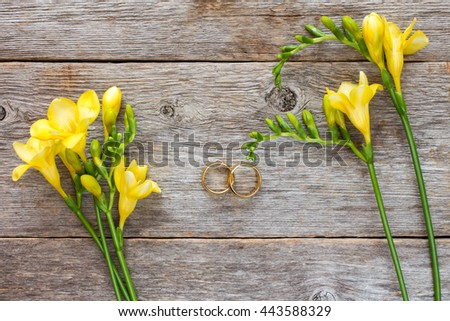 Wedding rings and freesia flowers on wooden background. Top view.
