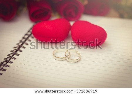 wedding rings and heart shape on white notebook space for your text. decoration idea love concept for valentines day - stock photo