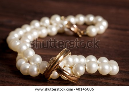 Wedding rings and pearls on wood for valentine's day